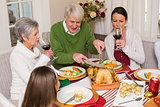 Grandfather carving chicken while women drinking red wine