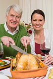 Grandfather carving chicken while woman drinking red wine