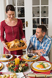 Woman serving roast turkey to her husband