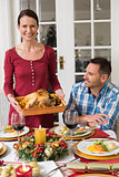 Couple smiling while woman holding roast turkey