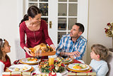 Woman serving roast turkey to her family