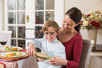 Little boy pulling a christmas cracker with his mother