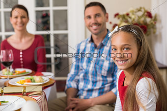 Portrait of cute girl with her parents behind