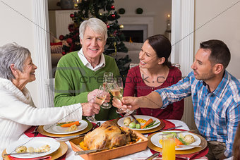 Portrait of happy family toasting at christmas dinner