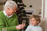 Grandfather showing glass of champagne to his grandson