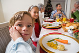 Portrait of little boy with a funny face at christmas dinner