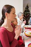 Extended family praying before christmas dinner