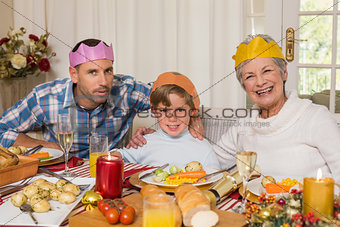 Portrait of grandmother father and son in party hat