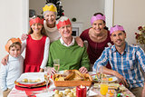 Happy extended family in party hat at dinner table