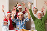 Happy extended family in santa hat cheering at camera