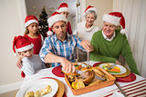 Father in santa hat carving chicken during dinner