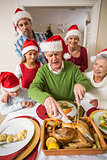 Grandfather in santa hat carving chicken during dinner