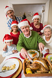Grandfather in santa hat carving chicken at christmas dinner