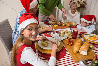 Portrait of cute girl in santa hat during christmas dinner