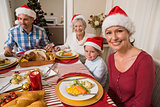 Happy family in santa hat during christmas dinner