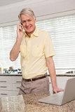 Senior man using his laptop on the phone
