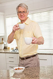 Senior man offering cup to camera