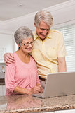 Senior couple using the laptop together