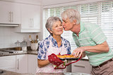 Senior man giving his wife a kiss while taking muffin