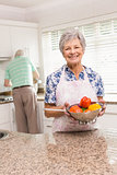 Senior woman showing colander of vegetables