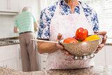 Senior woman showing colander of vegetables