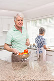 Senior man showing colander of vegetables