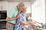 Senior couple washing vegetables at sink