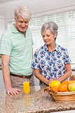 Senior couple looking at glass of orange juice
