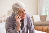 Senior man making a phone call on bed