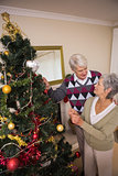 Senior couple decorating their christmas tree