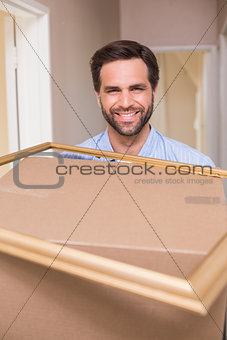 Happy man carrying moving box and frame