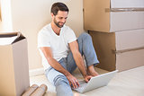 Happy man using laptop surrounded by boxes