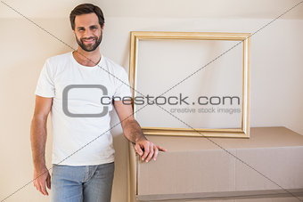 Happy man with moving boxes and frame