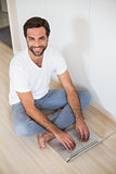 Happy man using laptop on floor