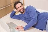 Happy man lying on floor using laptop