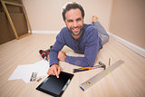 Casual man lying on floor using tablet pc for DIY instructions