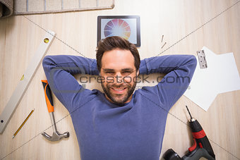 Casual man lying on floor surrounded by his diy tools