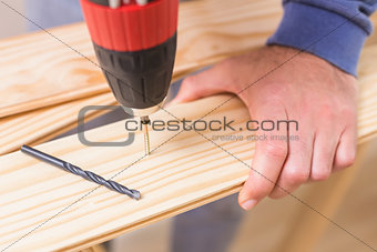 Casual man drilling hole in plank