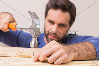 Casual man hammering nail in plank