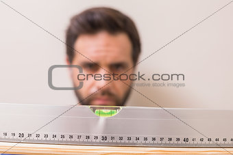 Casual man using spirit level