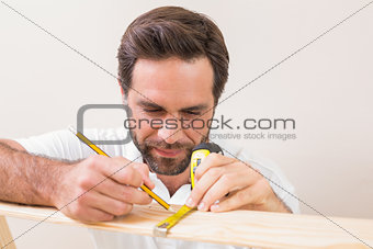 Casual man measuring plank of wood