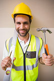 Construction worker holding spirit level and hammer