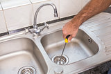 Man fixing sink with screwdriver