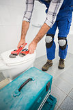 Plumber putting his tools on toilet