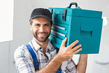 Plumber holding toolbox on shoulder