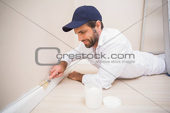 Painter painting the skirting boards