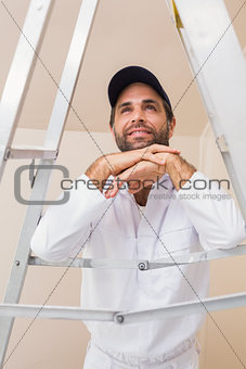 Painter smiling leaning on ladder