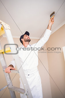 Painter standing on ladder painting roof
