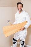 Carpenter holding planks and hammer
