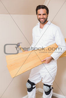 Carpenter holding planks and hammer